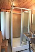 Saunarakennuksen suihkukoppi, jonka vieressä lämminvesivaraaja.