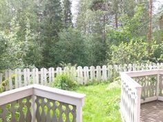 Takapiha on rajattu aidalla. Näkymät ovat metsäiselle viheralueelle