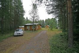 vasemmalla talon takana on saunarakennus ja liiteri. Oikealla aitta ja maakellari