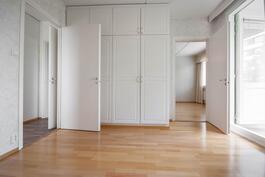 Makuuhuoneen kiinteät kaapistot. Näkymä olohuoneen puolelle ja kulku keittiöön sekä parvekkeelle.