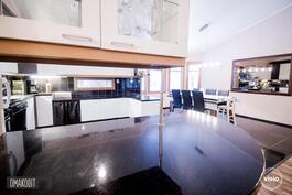 Mustavalkoisessa keittiössä kauniit kaapistot, työtasot mustaa graniittikiveä, saarekkeessa lasiovet
