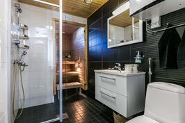 Kylpyhuoneessa on laadukkaat kalusteet ja upea musta laatta.