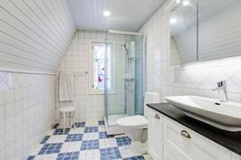 Yläkerran valoisassa, ylellisen kokoisessa kylpyhuoneessa suihkukaappi ja wc/kampauspiste.