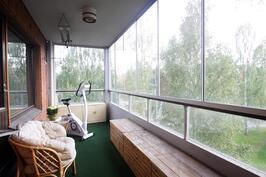 reilun kokoinen lasitettu parveke, josta vehreä näkymä eikä ketään vastassa