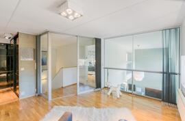 Yläkerran aulatilassa lasiseinät ja lamelliverhot - käytettävissä mainiosti myös makuuhuoneena