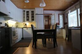 Tuvan keittio olohuoneesta, edessä pesuhuone/sauna, oikealla terassi
