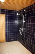 Alakerran laatoitettu kylpyhuone, jossa lattialämmitys.