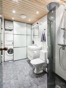 Alakerran kylpyhuoneessa liukuovien takana varaus pesutornille ja säilytystilaa