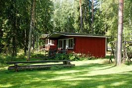 Kaksi mökkiä sijaitsee nurmikentän reunalla