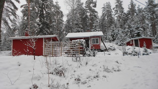 Mökki, sauna ja varasto talvipuvussaan.