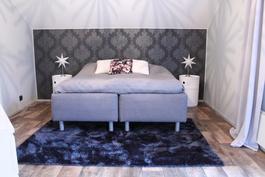Yläkerrassa tilava makuuhuone, josta käynti parvekkeelle