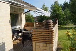 Aurinkoinen terassi, jonka saa suojaiseksi markiisilla.