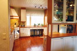 Tilava keittiö, jossa olohuoneen erottava tyylikäs lasivitriini.