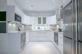Tilava keittiö jossa kivitaso ja laadukaat AEG laitteet.