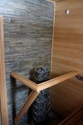 Saunassa laatoitettu kiviseinä