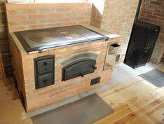 Muurattu liesi-leivinuuni RST-lämminvesisäiliöllä ja takana UPO-kamiina.