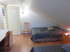 Yläkerran tilava toinen makuuhuone, jossa on 3 erillisvuodetta