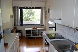 Keittiön ikkunan edessä parveke ja pihan leikkipaikka