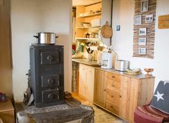 Keittiötä ja kamiina, jolla käyttövesi lämpiää kätevästi