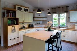 Puustellin vaniljanvärinen keittiö on tämänkin perheen komentokeskus.
