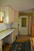Näkymä keittiöstä toiseen suuntaan eli komerolle ja ovelle