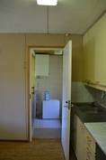 Näkymä keittiöstä pukuhuoneeseen, jossa myös pesukoneliitäntä