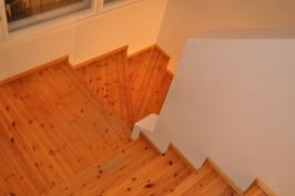 Mäntypuiset portaat johtavat yläkerran makuuhuoneisiin. Välitasanteen ikkunarivistö luo valoa.