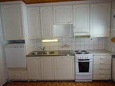 Valkoiset keittiön kaapistot ja koneet.