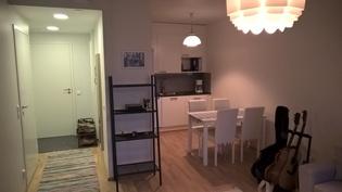 Keittiö ja eteinen olohuoneesta kuvattuna.