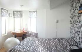 Yläkerran isompi makuuhuone. Huoneessa viihtyisä kulmaerkkeri.