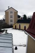 Maaliskuun lunta käytävän pikkuikkunasta piharakennusta päin