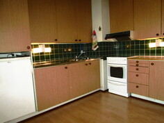 keittiö, jossa keraaminen liesi, liesituuletin, jääkaappi/pakastin -yhdistelmä sekä kaappipakastin
