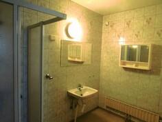 kylpyhuone, jossa suihkukaappi ja pesukoneliitin