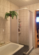 Kylpyhuone jossa sekä suihkukaappi että kylpyamme. Vesi tulee omasta kaivosta.