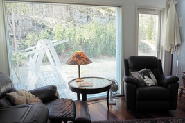 Tv/takkahuoneen suuresta ikkunasta näkyy oleskelupiha ja kauniit istutukset
