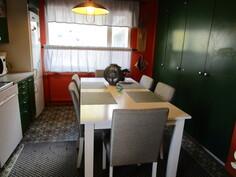 Keittiössä kaappeja kahdella seinällä, puupaneelikatto, sähköhella ja puuhella.