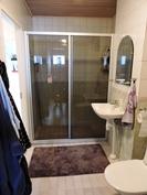 Tilavassa kylpyhuoneessa kätevä suihkuseinä.
