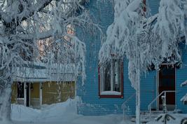 Päärakennuksen sokkelin tuuletusaukot peitetään talveksi pahvilla ja lumi eristää alapohjan.