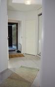 Takimmaisena näkyy avoin ulko-ovi. Tuulikaapin vieressä on sisävarasto/vaatehuone.
