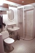 Vaaleasävyinen kylpyhuone, jossa on myös hyvin kaappitilaa.