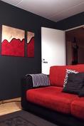 Tilava olohuone on pääosin maalattu harmonisella harmaalla. Huoneeseen on käynti myös eteisestä.