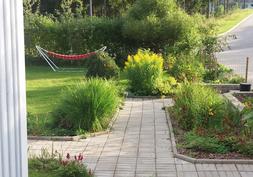 Kulkuväylät on laatoitettu. Varrella kasvaa iiristä, kultapiiskua ja liljoja.