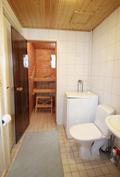 Näkymä pesuhuoneesta saunaan, jossa lasiovi ja tuuletusikkuna, vasemmalla ovi eteiseen