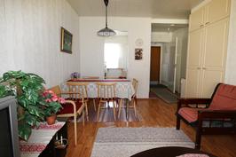 Näkymä puutarhaovelta olohuoneeseen, taustalla ikkunallinen keittokomero (vas.) ja eteinen