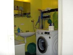 näkymä kylpyhuoneen lavuaari- ja pesukonenurkasta
