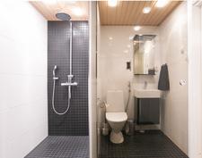 Kylpyhuoneessa kattosuihku sekä pieni wc, välissä kätevä lasiliukuovi.