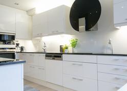 Keittiössä kauniit mustat kivitasot ja moderni liesituuletin.