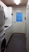 Kodihoitohuone, josta käynti ulos, pesuhuoneeseen ja saunaan.