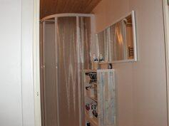 Kylpyhuoneessa on suihkukaappi ja paikka pesukoneelle
