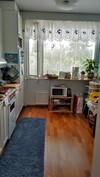 Keittiö jossa liesi, jääkaappi ja runsaasti kaappitilaa